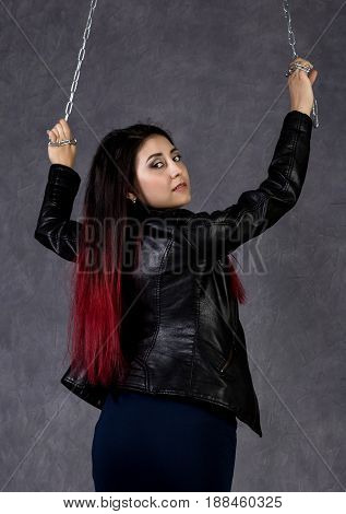 sexy asian woman wearing leather jacket and black skirt holding a chain and posing on a gray background.