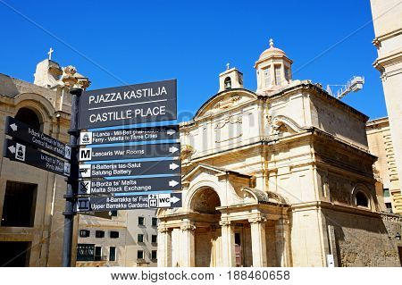 VALLETTA, MALTA - MARCH 30, 2017 - St Catherine of Alexandria Church with a places of interest sign in the foreground Valletta Malta Europe, March 30, 2017.