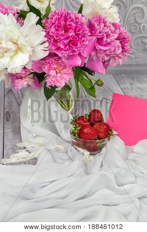 Strawberries with a bouquet of peonies on a grey background