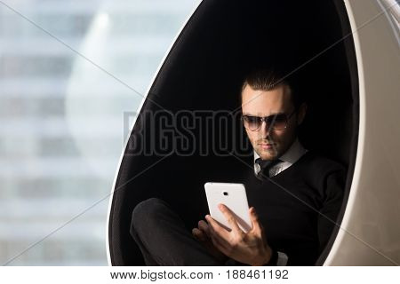 Young attractive model guy in sunglasses and stylish formal wear sitting in comfortable egg chair and looking on tablet computer in his hands. Businessman reads e-book, revising meetings schedule