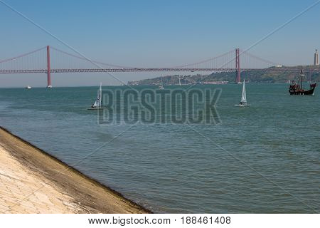 25th April Bridge in Lisbon over the Tagus River and Sailing Boats Portugal