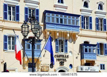 VALLETTA, MALTA - MARCH 30, 2017 - The Castille Hotel with a Maltese and EU flag in the foreground Valletta Malta Europe, March 30, 2017.