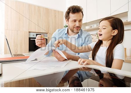 Need some help. Pleasant pretty girl staying near her father, trying to help him by pointing at the printout and explaining something while he listening to her attentively.