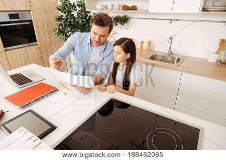 Totally involved. Pretty little daughter paying close attention to her father explaining work issues to her via pointing at a sheet of paper.