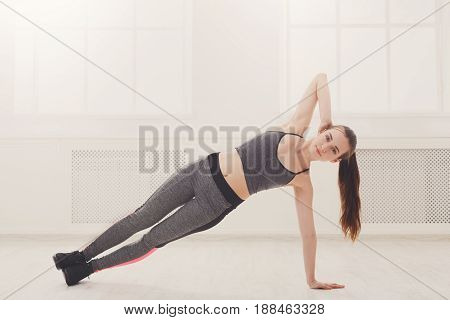 Fitness woman side plank workout training at white background indoors. Young slim girl makes exercise.
