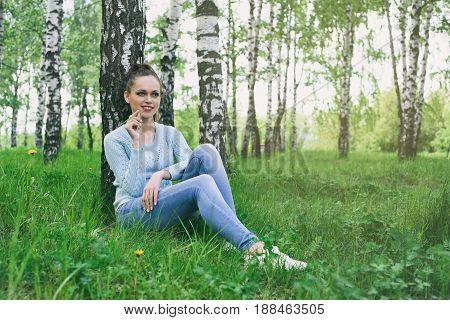 Happy Girl Sitting On A Green Grass In The Park