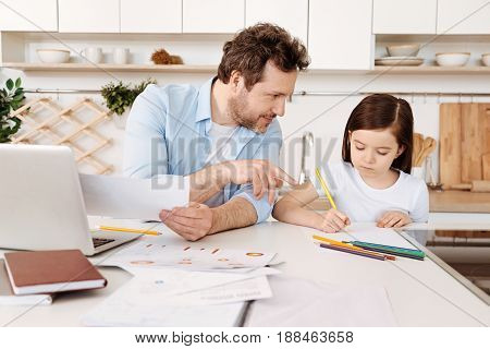 Creative process. Smiling young father pointing the finger at the drawing of his daughter as if suggesting some pieces of advice to her while she keeping eyes fixed on the sheet of paper.