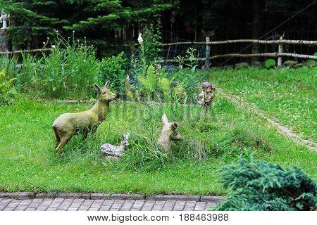 Decorative figures of deer family and kids in the garden