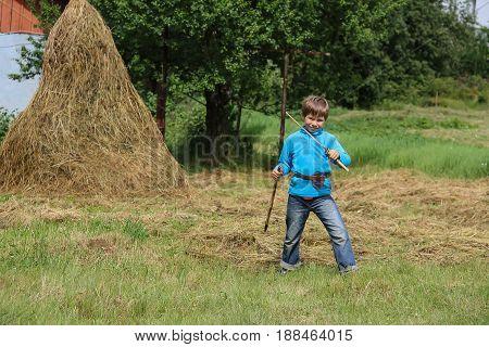 Boy with wooden sword near haystack on green lawn
