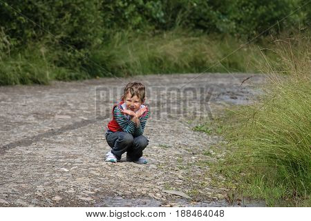 Crouching smiling boy in summer forest park