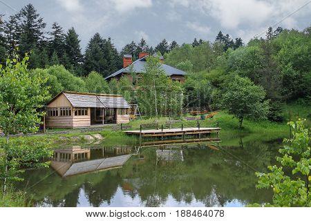 Modern cottage and a gazebo on shore of lake in Ukrainian Carpathians