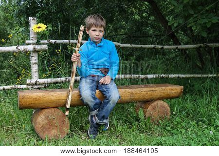 Boy with wooden sword sitting on log bench
