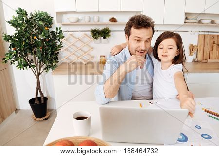 Curious glances. Smiling little girl hugging her father with one hand and pointing at something amusing on the laptop while her father looking at it with a curious, surprised expression.