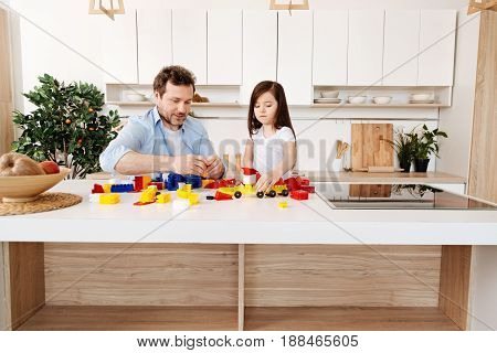 Absolutely concentrated. Young bristled father and daughter sitting in the kitchen at a white counter full of construction set parts, assembling them