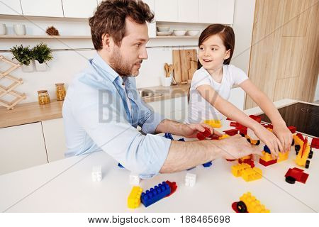 Having fun. Young single parent and his little daughter assembling together a construction set, enjoying themselves and looking at each other with a playful expression while smiling