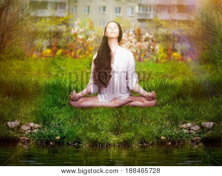 Beautiful girl is engaged in yoga. Meditation on nature in the city Park