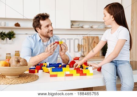 Showing togetherness. Cute little girl sitting on the top of the counter and building a wall with a construction set while her father putting together two parts of distinct colours