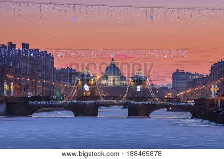 St. Petersburg Lomonosov Bridge across the Fontanka River and Trinity Cathedral at sunset Christmas illumination