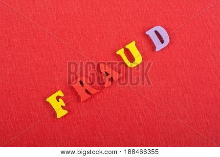 FRAUD word on red background composed from colorful abc alphabet block wooden letters, copy space for ad text. Learning english concept