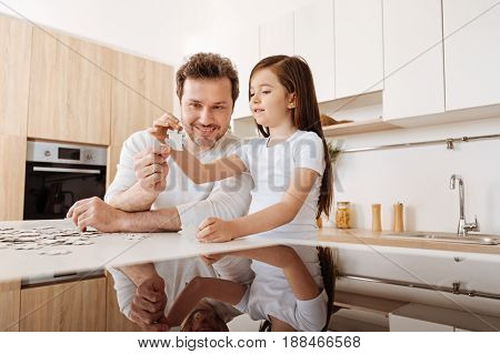 Working together. Cheerful smiling father and his pleasant little daughter holding two jigsaw puzzle pieces together and their images being reflected on the glass surface in the bottom of the photo.