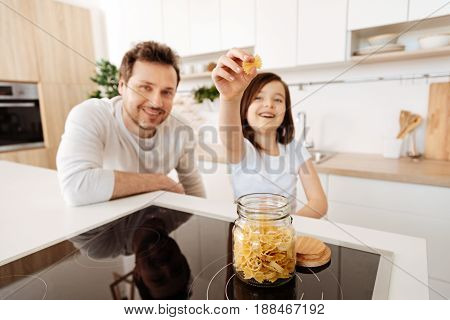 Pasta lover. Pretty cute girl standing in the kitchen and holding a piece of farfalle pasta from the jar placed on the cooktop while her father looking into the camera and smiling