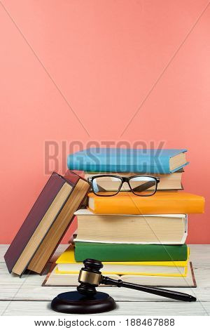 Law concept open book with wooden judges gavel on table in a courtroom or law enforcement office, pink background. Copy space for text