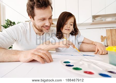 Creative atmosphere. Bristled handsome man sitting at the kitchen desk with a palette and a water container, bonding to his petite daughter while watching her painting with blue watercolour
