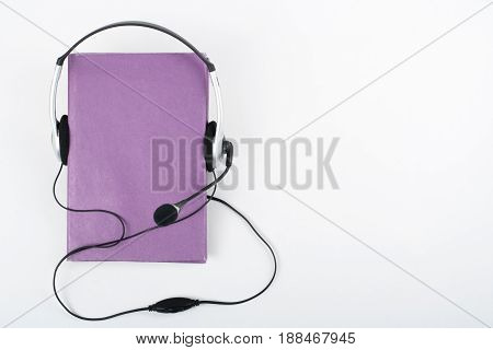 Audiobook on white background. Headphones put over purple hardback book, empty cover, copy space for ad text. Distance education, e-learning concept