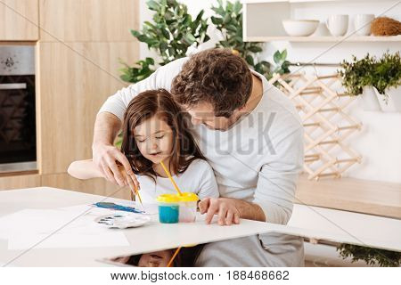 Fatherly care. Curly bristled father standing in the kitchen behind his little daughter and holding her hand with a brush, while she painting a watercolour picture.