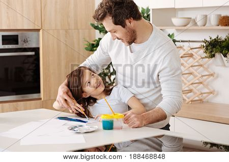 Fondly looks. Sweet young father standing behind his little daughter, holding her hand with a brush, hugging and smiling to her while she turning her head to him