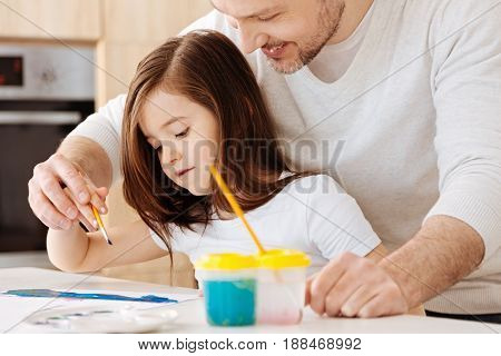 Tenderness of a touch. Caring and loving father holding a hand of his little daughter while she putting strokes on her watercolour painting