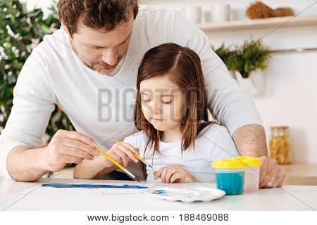 Best time. Gentle caring father helping his favourite daughter in painting a watercolour picture by putting some strokes on the sheet himself