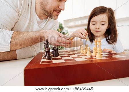 Mutual aid. Cute little girl helping her father with a chessboard setup by putting pieces onto their places while the father handing her one