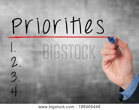 Business Man Hand Writing Priorities List With Marker Isolated On Grey