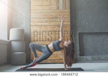 Woman in side plank at yoga class, Vasisthasana exercise. Fit yogi girl balancing on mat indoors at fitness studio gym