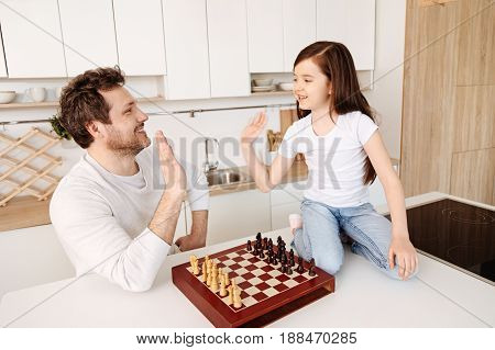 High five. Content young father giving his cute little daughter a high five after finishing a chess game while both of them smiling at each other