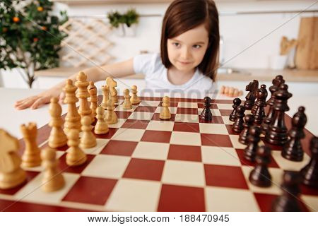 New vision. The focus being on the chessboard with two pawns in the middle while the background having a creative smart girl looking at the chessboard under a different angle