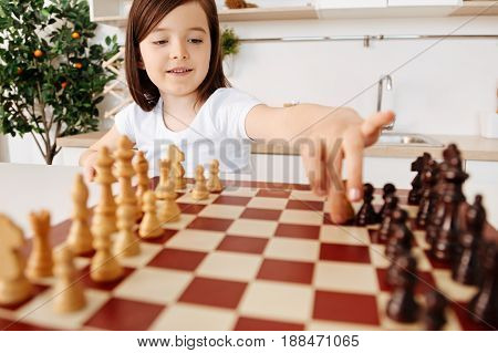 Best game. Cute smart girl reaching out her hand for moving a white pawn while playing along at the chessboard