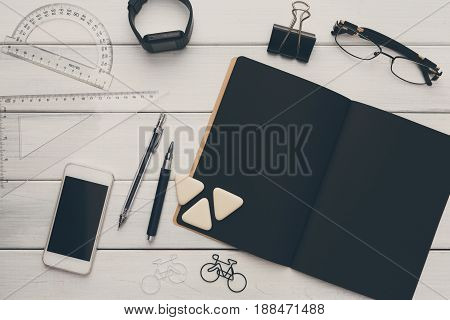 Education, office and work concept, top view of black and white workplace. Stationery supplies - blank notepad, pens, binder clips, phone, watch on wooden desktop, flat lay, copy space, template