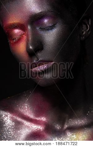 Beautiful girl with art space makeup on her face and body. Glitter Face. Photo taken in the studio.
