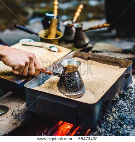 Man Is Cooking Turkish Coffee In The Box With Sand Under Live Coals