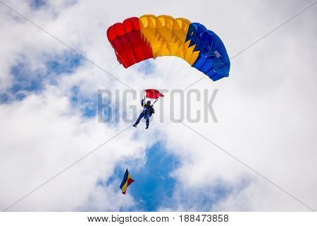 Man landing with parachute colored with Romanian flag