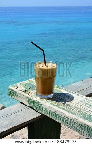 Greek frappe ice coffee with straw on grunge green wooden rest agains blue sea background in ahot sunny day