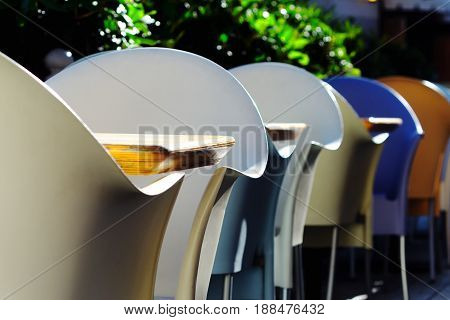 Plastic multi-colored chairs and wooden tables in a summer cafe