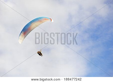 Para glider is soaring in fight hovers into a cloudy sky blue and white style of Para glider