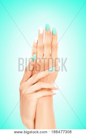 Well-groomed female hands with mint-white manicure on a turquoise background