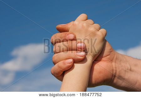 Handshake of a child and an adult against a blue sky.