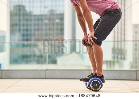 Guy on gyroscooter outdoors. Legs and hoverboard.