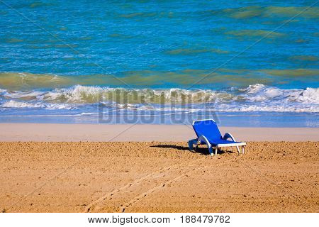 Summer. The shore of the ocean. One blue trestle-bed stands in the surf zone. Sand and wave