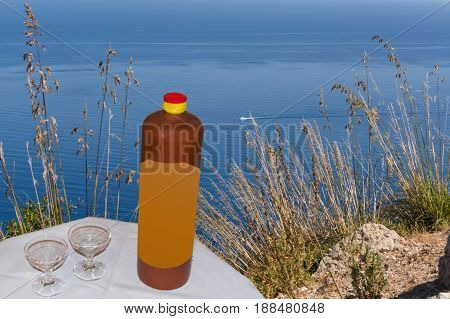 Ceramic bottle with two liqueurs on a small table in the background the blue sea and a sport boat.